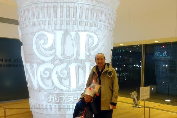 Artist Marten Go with son, Jerome Ng standing in front of huge cup noodle statue at the Cup Noodle Museum in Yokohama, Japan