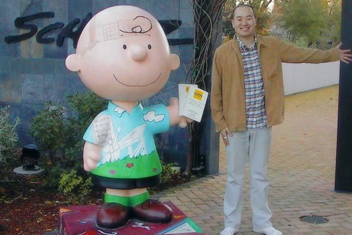 Aritst Marten Go standing next to large human scale Charlie Brown at the Peanuts Museum in Santa Rosa, California