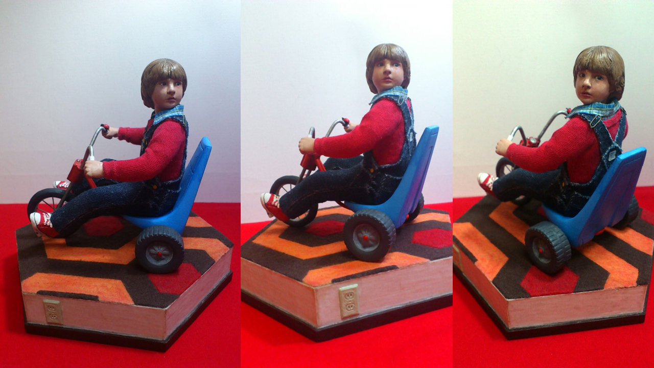 Three images side by side by side in full body shots of the completed miniature statue of Danny Torrance in various angles on base