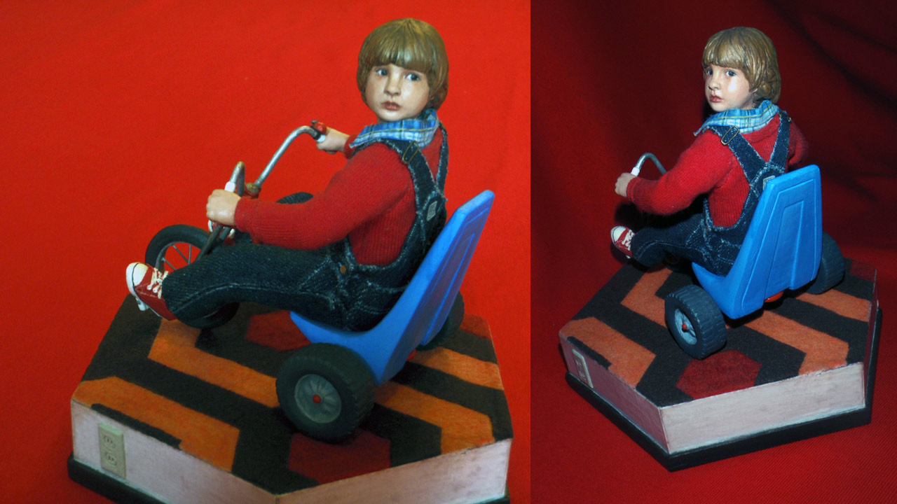 Two images side by side in full body shots of the completed miniature statue of Danny Torrance with red background