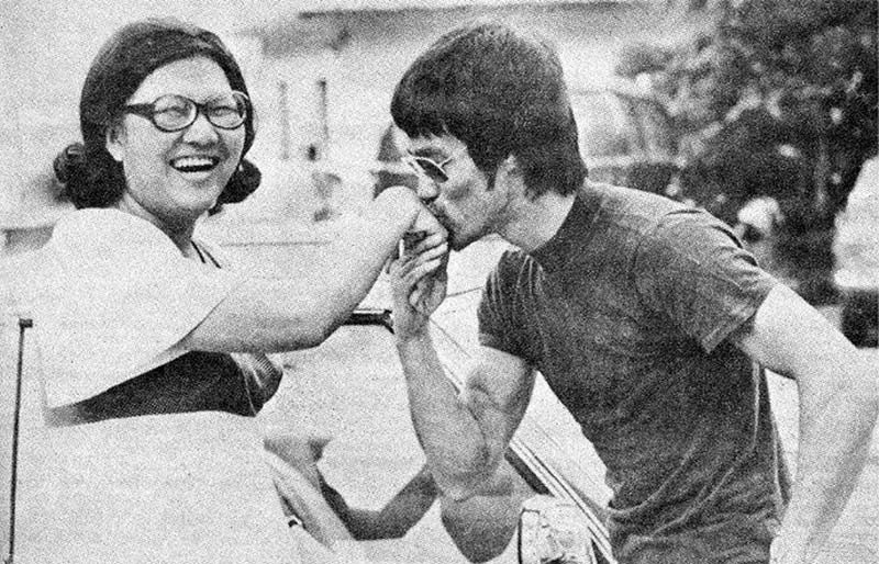 Black and white photo of the Master Bruce Lee kissing the hand of a very lucky fan
