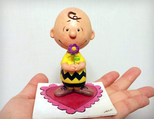 Charlie Brown from The Peanuts holding a purple flower standing on a Valentine's heart theme base statue by Marten Go aka MGO in his palm