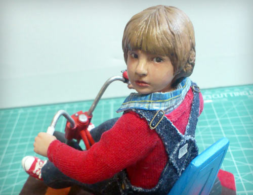 Danny Lloyd as Danny Torrance in the Stephen King novel adapted by Stanley Kubrick looking back over shoulder seated on big wheel statue by Marten Go aka MGO