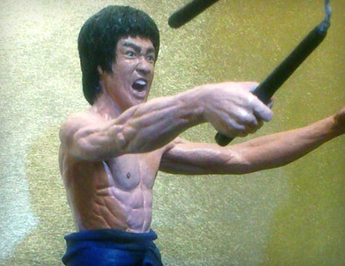 Bruce Lee as Mr. LEE in the martial arts classic Enter the Dragon with one hand out and other clutching nunchaku in attack motion statue by Marten Go aka MGO