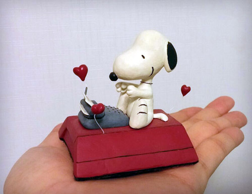 Snoopy from The Peanuts siting on his red dog house typing on little typewriter statue by Marten Go aka MGO in his palm