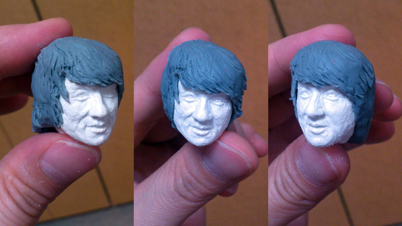 Three close up images side by side by side of the miniature refined sculpted head of Thomas with pronounced facial details and stand-in hair